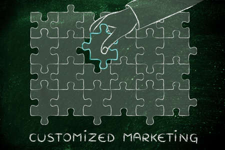 customized: Customized Marketing: metaphor of hand completing a puzzle Stock Photo