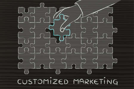 completing: Customized Marketing: metaphor of hand completing a puzzle Stock Photo