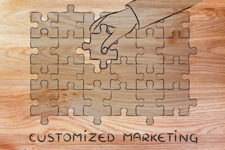 complete solution: Customized Marketing: metaphor of hand completing a puzzle Stock Photo