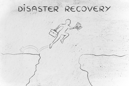 disaster recovery: disaster recovery: businessman  jumpying over a cliff holding business plan and laptop bag Stock Photo