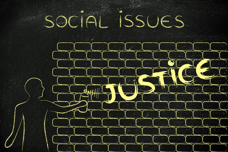 social issues: person with spray paint writing the word Justice as wall graffiti, social issues theme