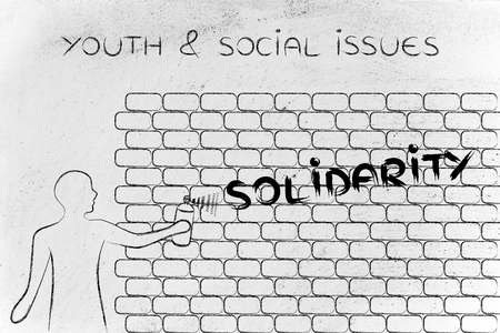 social issues: person with spray paint writing the word Solidarity as wall graffiti, youth & social issues