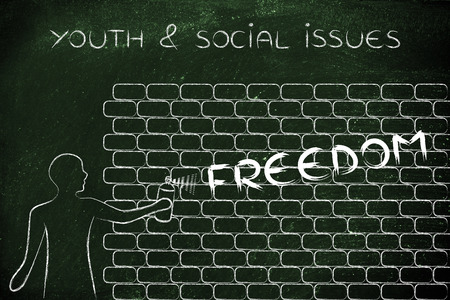 social issues: person with spray paint writing the word Freedom as wall graffiti, youth & social issues