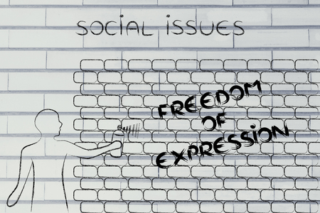 social issues: person with spray paint writing the word Freedom of Expression as wall graffiti, social issues