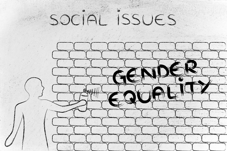 social issues: person with spray paint writing the word Gender Equality as wall graffiti, social issues theme