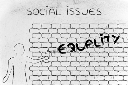 social issues: person with spray paint writing the word Equality as wall graffiti, social issues theme Stock Photo