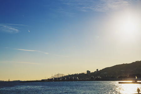 CANNES, FRANCE - 30 January, 2016: Mediterranean sea view from Golfe Juan at dusk with sun flare, with the Lerins Islands, the harbour and Canness coastline in the distance