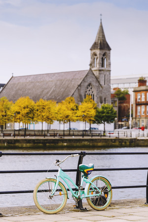 leinster: DUBLIN, IRELAND - Septembter 27th, 2016: View over the river Liffey walk featuring a blue bike and unfocused church in the background Editorial