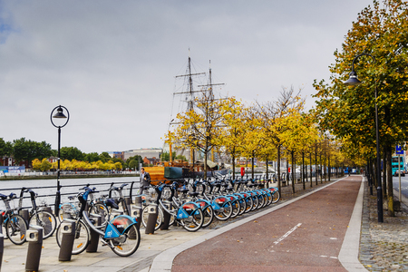 DUBLIN, IRELAND - Septembter 27th, 2016: View over the river Liffey walk featuring autumn coloured trees and city bikes in Dublin One district Editorial