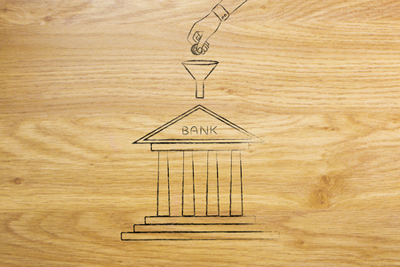 expenditure: hand dropping coins into funnel above bank building, concept of adding savings to your bank account Stock Photo