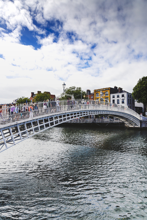 DUBLIN, IRELAND - July 15th , 2017: view of the historical HaPenny Bridge over the River Liffey in Dublin, Ireland (with unidentified people)
