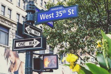 NEW YORK, NY - 2 settembre 2017: La lampada di via e West 35th Street firmano dentro Manhattan con il bokeh del tabellone per le affissioni e del fiore Archivio Fotografico - 86777180