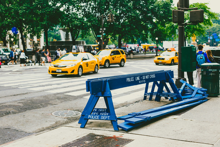 NEW YORK, NY - June 9th, 2014: Police do not corss road sign stored on the sidewalk in Manhattan with traffic bokeh
