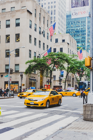 NEW YORK, NY - June 9th, 2014: detail of the 5th Avenue west 49th street in Manhattan with yellow cabs and american flags waving from the buildings