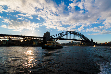 SYDNEY, AUSTRALIA - July 12th, 2013: Sydney Harbour Bridge at sunset with sun flare shot from the ferry Editorial