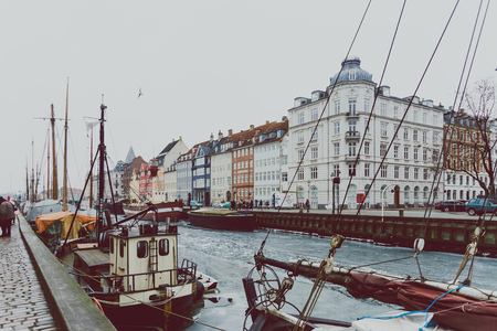 COPENHAGEN, DENMARK - March 11th, 2018: Copenhagen's famous Nyhavn harbour with the typical colorful houses and restaurants along the iced canals with traditional boats