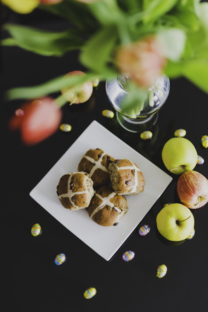 hot cross buns and chocolate eggs next to apples and flowers on indoor Easter table setting Stock Photo