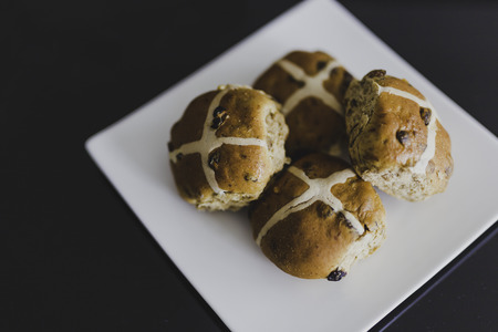 hot cross buns on black table, close-up shot with shallow depth of field