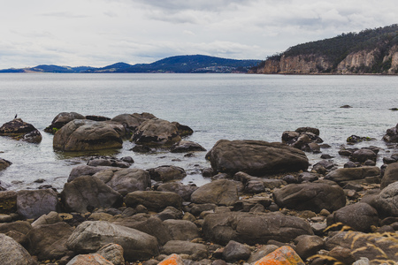 deserted beach in Hobart, Tasmania with rocks in the foreground on an overcast day with slightly muted tones