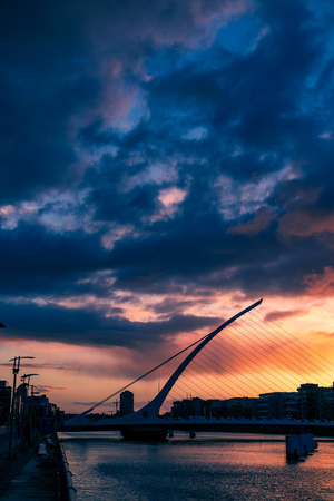 DUBLIN, IRELAND - May 9th, 2018: Majestic orange and pink toned sunset over the river Liffey in Dublin, featuring the Samuel Beckett bridge