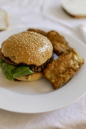 veggie burger bun with courgette fritters on white table setting shot at shallow depth of field Фото со стока