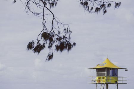 GOLD COAST, AUSTRALIA - January 7th, 2015: yellow lifeguard hut with branches in the foreground and overcast sky Editorial
