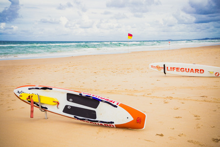 GOLD COAST, AUSTRALIA - January 5th, 2015: lifeguard surfboard on the beach in Surfers Paradise on an overcast day with golden sand and covered sky above the Pacific Ocean