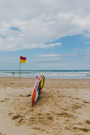 GOLD COAST, AUSTRALIA - January 14th, 2015: lifeguard surfboard and lifesaving flag on the beach in Surfers Paradise Editorial