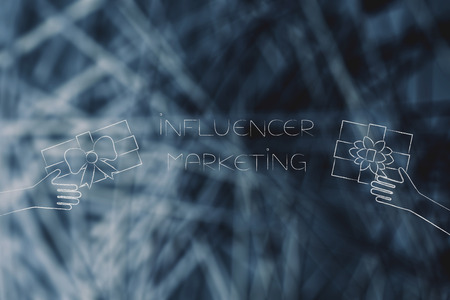 social media marketing conceptual illustration: influencer marketing text with PR gifts being handed at it Stock Photo