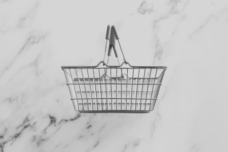 empty grocery store shopping basket isolated on marble surface