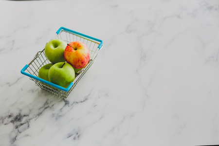 grocery store mini shopping basket with one single red apple among other green ones, concept of picking the best produce