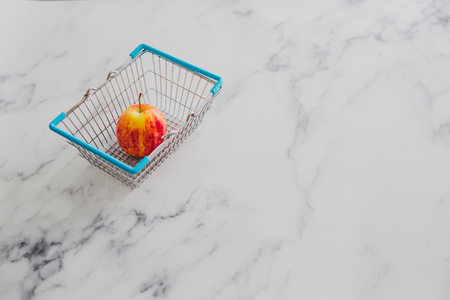 grocery store mini shopping basket with one single red apple and marble surface background, concept of healthy diet