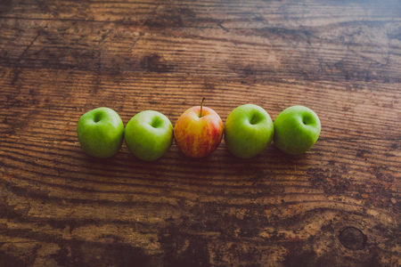 one single red apple among other green ones on wooden table, concept of choosing the best produce