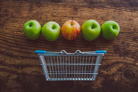 grocery store mini shopping basket with one single red apple among other green ones on wooden table, concept of picking the best produce Stock Photo