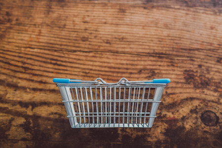 empty grocery store shopping basket on wooden surface Stock Photo