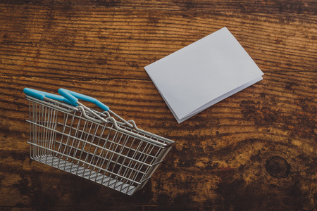 empty shopping basket with copyspace on memo paper and wooden surface background