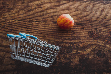grocery store mini shopping basket with one single red apple and wooden surface background, concept of healthy diet