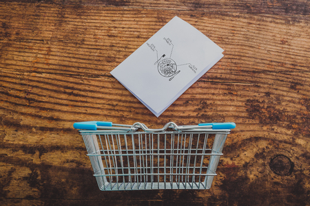 shopping basket and healthy food portion note on memo paper on wooden table, concept of nutrition and diet Stock Photo