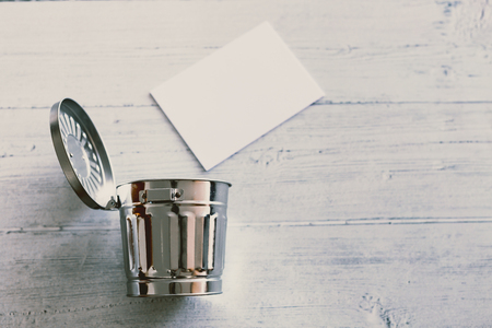 silver trash can semi-opened and paper with copyspace going into it Stock Photo
