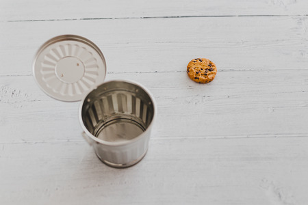 cookie next to a trash can, metaphor about website cookies and user tracking technologies