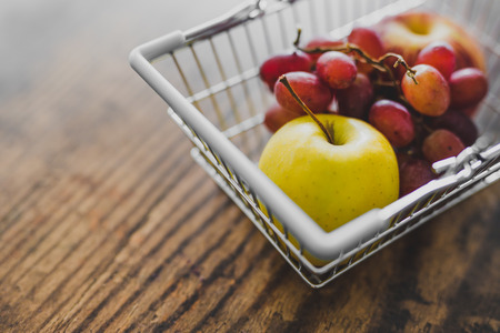 shopping basket on wooden table with fresh healthy fruit in it