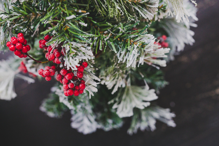 detail of small Christmas tree with snow mistletoe and pine cone decorations, cozy festive winter holidays feeling