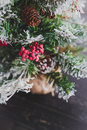 Christmas tree with pine cones and mistletoes berries and hints of snow on the branches, cozy festive winter holidays feeling