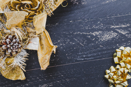 golden Christmas decoration with pine cones and gift ribbons on dark wooden surface Stock Photo