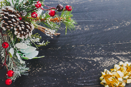 pine cones and mistletoe decoration framing the corner of the image on wooden table with copyspace for your text