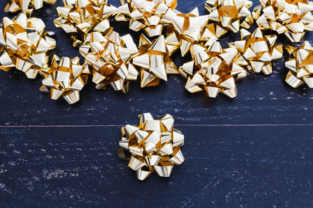 golden gift wrapping ribbon decorations on dark wooden surface, Christmas or birthday themed
