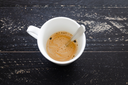 white cup of coffee with foam and spoon from above on dark wooden surface with vignette