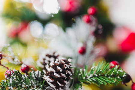 Christmas pine cone and mistletoe decoration with bokeh of xmas tree in the background shot at shallow depth of field