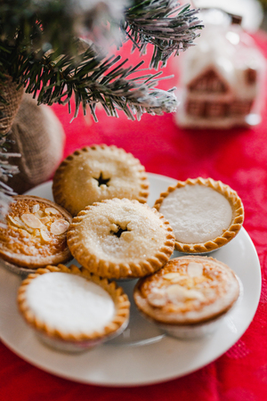 mince pies on Christmas table setting with decorations and tree bokeh shot at shallow depth of field