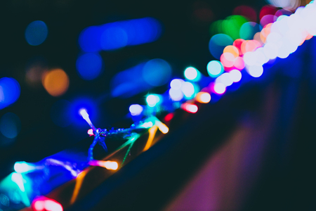 string of multicolored fairy lights on house terrace with bokeh effect and other street lights in the background Stock Photo